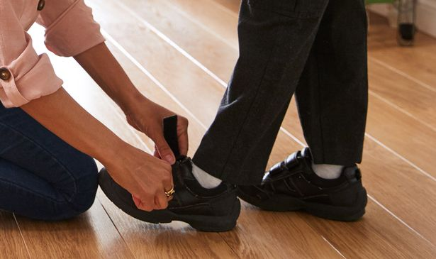 Mum putting on her son's shoes for school