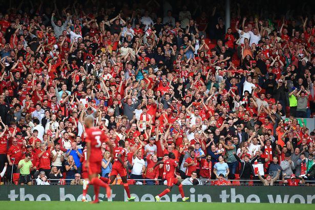Liverpool fans go wild as Sadio Mane of Liverpool celebrates after scoring their 1st goal during the Premier League match between Liverpool and Crystal Palace at Anfield on September 18, 2021 in Liverpool, England.