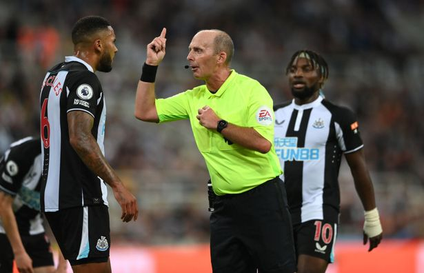 Referee Mike Dean has words with Jamaal Lascelles during the Premier League match between Newcastle United and Leeds United at St. James Park on September 17, 2021 in Newcastle upon Tyne, England.
