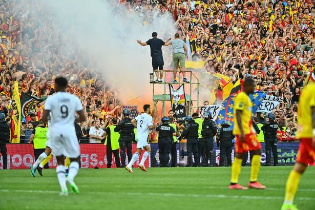 Fans of Lens light up flares under the eyes of policemen during the Ligue 1 Uber Eats match between Lens and Lille at Stade Bollaert-Delelis on September 18, 2021 in Lens, France.