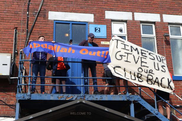 Fans protest outside the stadium against Oldham Athletic owner Abdallah Lemsagem prior to the Sky Bet League Two match between Oldham Athletic and Hartlepool United at Boundary Park on September 18, 2021 in Oldham, England.