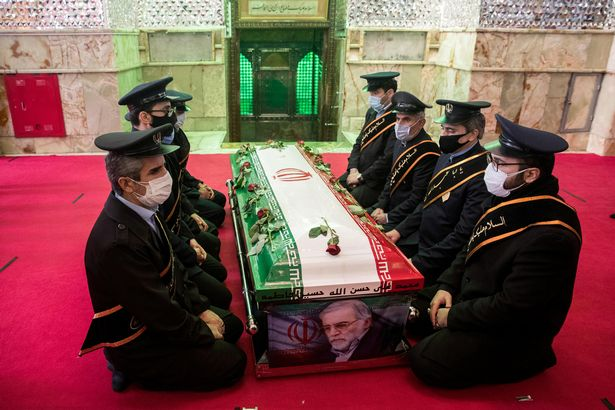 Mourners kneel by Fakhrizadeh's coffin
