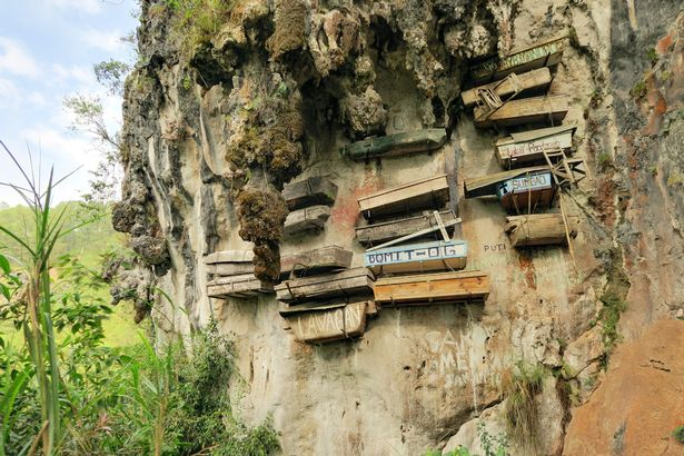 Hundreds of wooden coffins dangle from cliffs and caves