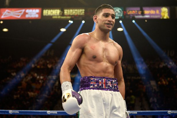 Amir Khan smiles as he heads to his corner while taking on Luis Collazo during their welterweight bout at the MGM Grand Garden Arena on May 3, 2014 in Las Vegas, Nevada.