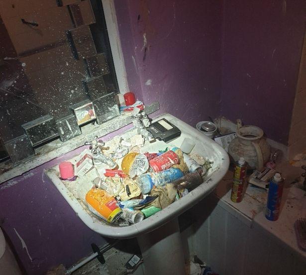 A bathroom sink full of rubbish