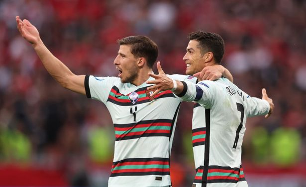 Cristiano Ronaldo of Portugal celebrates with team mate Ruben Dias after scoring their side's third goal during the UEFA Euro 2020 Championship Group F match between Hungary and Portugal at Puskas Arena on June 15, 2021 in Budapest, Hungary