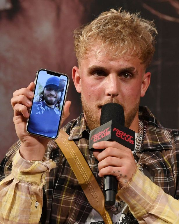 Jake Paul talks to mixed martial artist Jorge Masvidal on his cell phone during a news conference for Triller Fight Club's inaugural 2021 boxing event at The Venetian Las Vegas on March 26, 2021 in Las Vegas, Nevada.