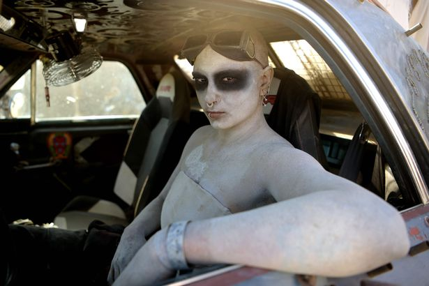 A woman poses for pictures in her car during Wasteland Weekend festival at the Mojave desert in Edwards, California