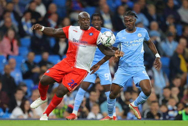 Adebayo Akinfenwa of Wycombe Wanderers F.C. and Romeo Lavia of Manchester City battle for the ball during the Carabao Cup Third Round match between Manchester City and Wycombe Wanderers F.C. at Etihad Stadium on September 21, 2021 in Manchester, England.