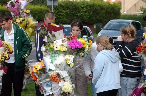 Friends of Conman's look at the flowers laid at the scene of the murder in 2006