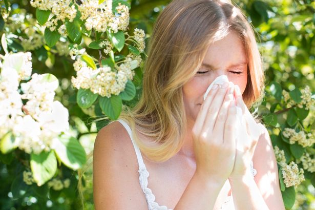 Young woman blowing nose on tissue