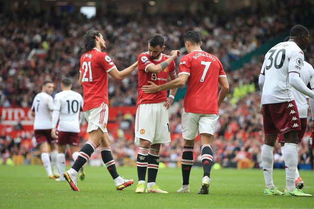 Bruno Fernandes of Manchester United (C) is consoled by teammates Edinson Cavani of Manchester United (L) and Cristiano Ronaldo of Manchester United after missing his penalty during the Premier League match between Manchester United and Aston Villa at Old Trafford on September 25, 2021 in Manchester, England.