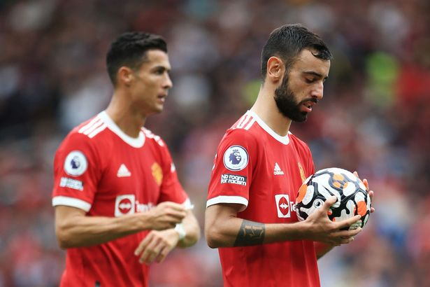 Bruno Fernandes of Manchester United (R) prepares to take his penalty as Cristiano Ronaldo of Manchester United looks on during the Premier League match between Manchester United and Aston Villa at Old Trafford on September 25, 2021 in Manchester, England.