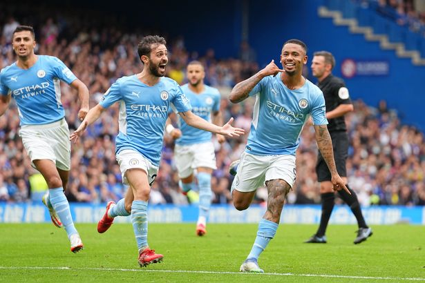 Gabriel Jesus of Manchester City (R) celebrates with teammate Bernardo Silva after scoring their team's first goal during the Premier League match between Chelsea and Manchester City at Stamford Bridge on September 25, 2021