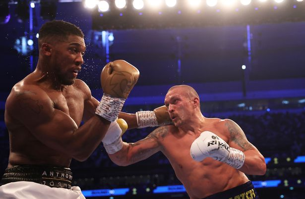 Oleksandr Usyk punches as Anthony Joshua ducks during the Heavyweight Title Fight between Anthony Joshua and Oleksandr Usyk at Tottenham Hotspur Stadium on September 25, 2021 in London, England