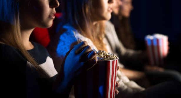 Teenager friends at the cinema watching a movie together and eating popcorn, beautiful girl on foreground, movies and entertainment concept