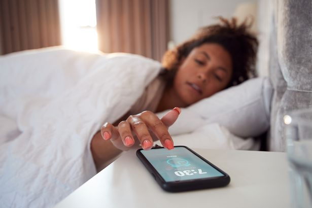 Woman waking up in bed reaching for her phone