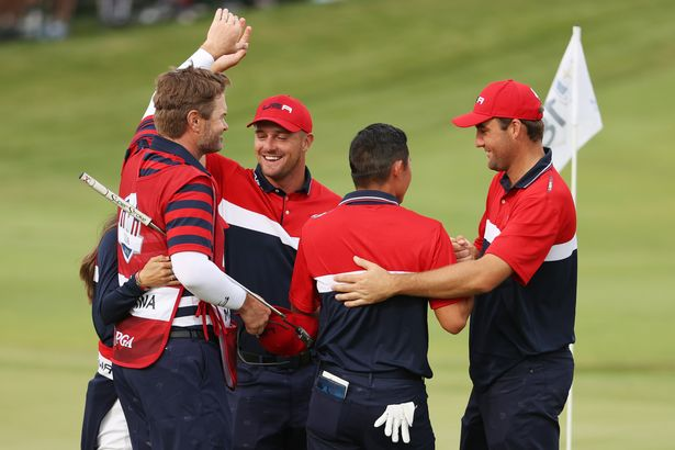 Collin Morikawa of team United States celebrates on the 18th green with caddie J.J. Jakovac, girlfriend Katherine Zhu, Bryson DeChambeau of team United States and Scottie Scheffler of team United States after winning the half point needed to win during Sunday Singles Matches of the 43rd Ryder Cup at Whistling Straits