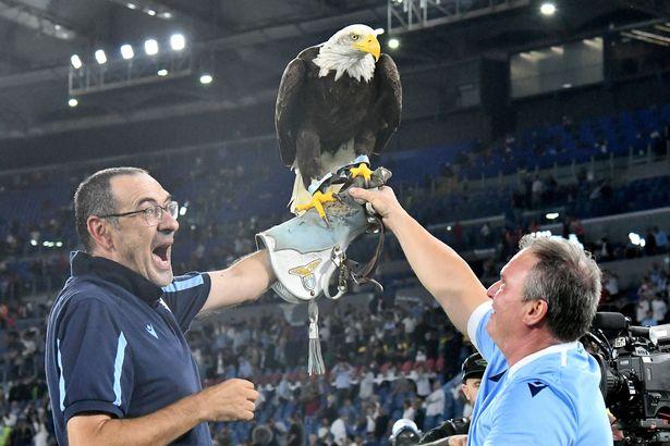 Lazio's Italian coach Maurizio Sarri (L) celebrates with Lazio's eagle mascotte Olimpia at the end the Italian Serie A football match Lazio vs AS Roma at the Olympic stadium in Rome on September 26, 2021.