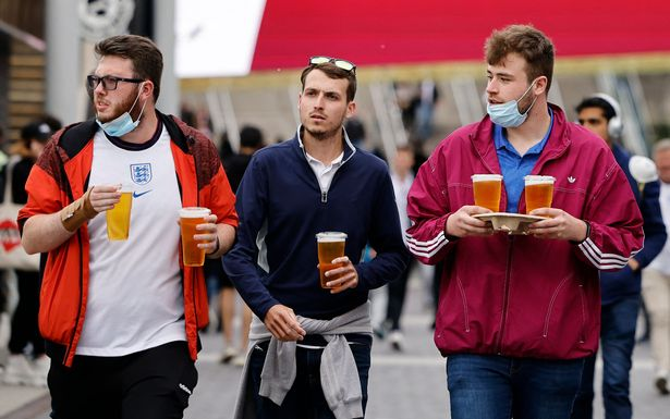 England supporters carry pints of beer as they arrive at Wembley Stadium in west London on June 22, 2021, to watch the UEFA EURO 2020 football match between England and Czech Republic