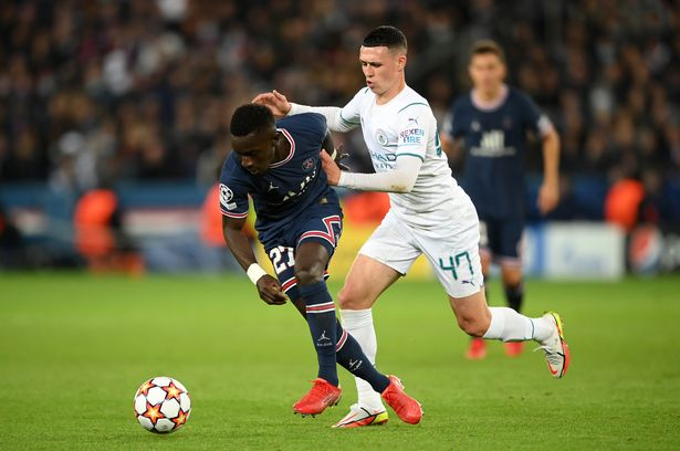 PARIS, FRANCE - SEPTEMBER 28: Idrissa Gueye of Paris Saint-Germain is challenged by Phil Foden of Manchester City during the UEFA Champions League group A match between Paris Saint-Germain and Manchester City at Parc des Princes on September 28, 2021 in Paris, France. (Photo by Matthias Hangst/Getty Images)