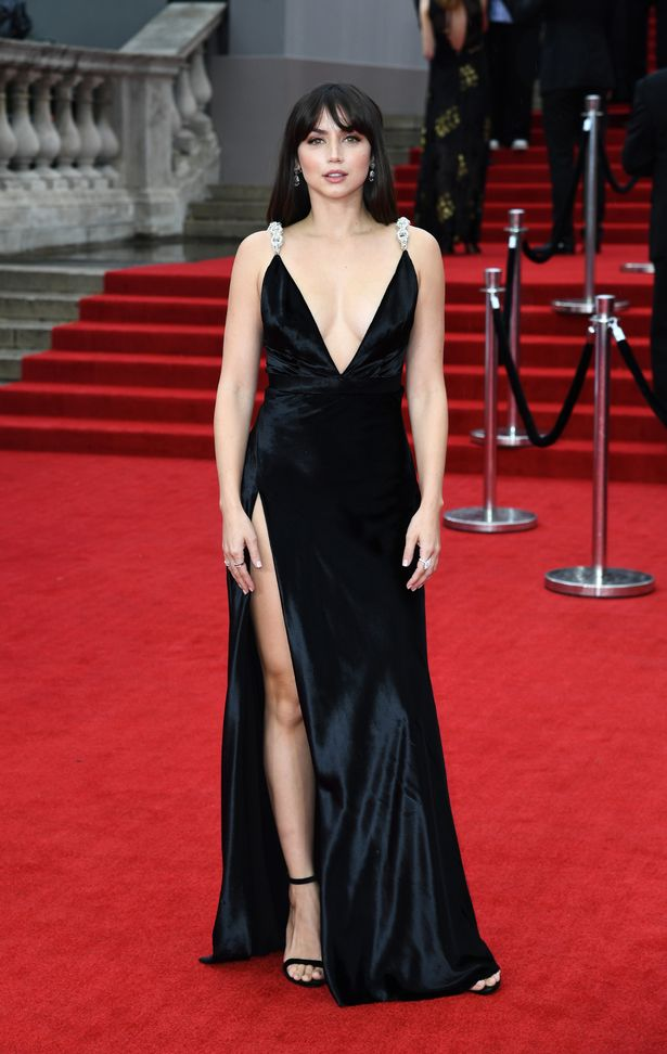 The Bond girl showcased her stunning figure in a low-cut black gown with a risqué thigh-split