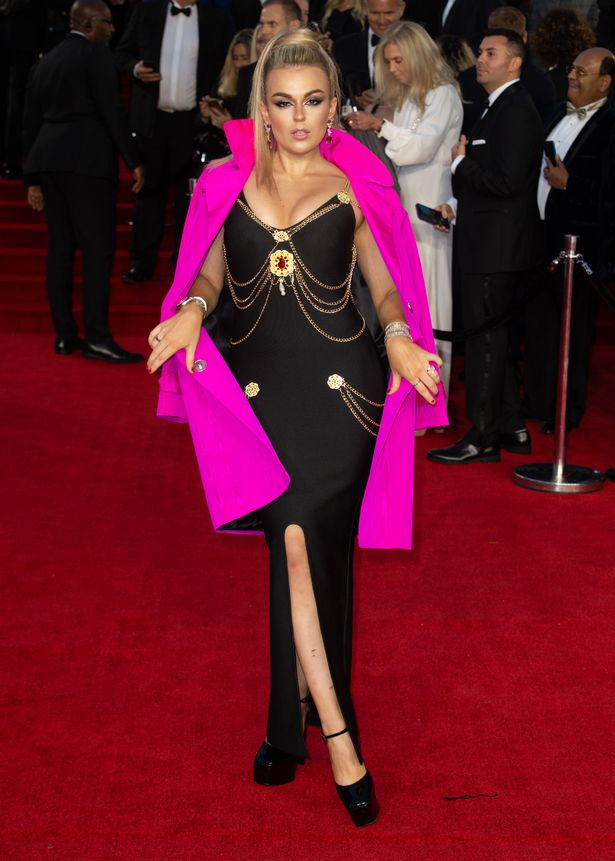 Musician Tallia posed up a storm on the red carpet in a tight dress with a bright pink overcoat
