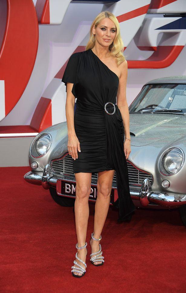Tess flashed her endless bronzed legs in a stunning black asymmetrical mini dress