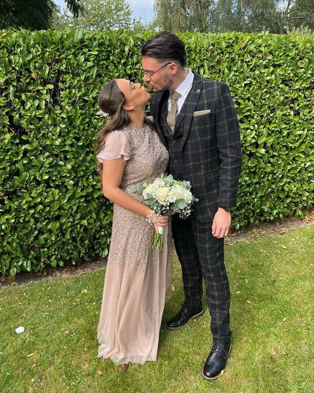 Corrie's Ellie Leach and her beau Reagan Pettman lean in for a quick kiss at a mate's wedding
