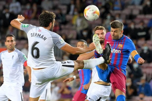 Granada's Spanish defender German vies with Barcelona's Spanish defender Gerard Pique (R) during the Spanish League football match between FC Barcelona and Granada at the Camp Nou stadium in Barcelona on September 20, 2021