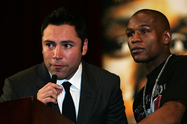 Promoter Oscar De La Hoya speaks alongside Floyd Mayweather Jr. during the post fight news conference after Mayweather defeated Ricky Hatton of England in the 10th round after their WBC world welterweight championship fight at the MGM Grand Garden Arena