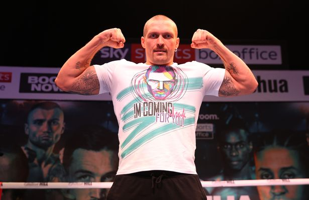 Oleksandr Usyk flexes during press duties for his fight against Anthony Joshua
