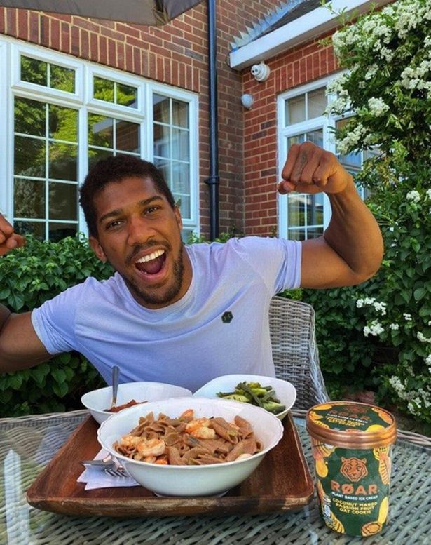 Anthony Joshua posing in front of some food