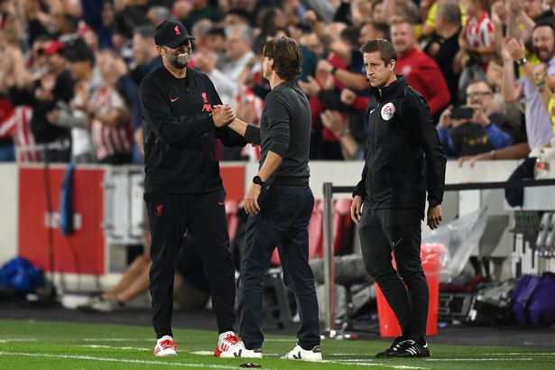 Jurgen Klopp, Manager of Liverpool and Thomas Frank, Manager of Brentford embrace after the final whistle during the Premier League match between Brentford and Liverpool at Brentford Community Stadium on September 25, 2021 in Brentford, England.