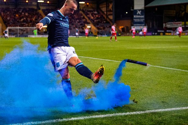 Dundee's Leigh Griffiths kicks a blue smoke bomb thrown on by St Johnstone fans during a Premier Sports Cup quarter-final match between Dundee and St Johnstone at the Kilmac Stadium at Dens Park, on September 22, 2021, in Dundee, Scotland.