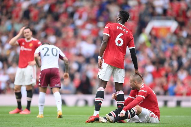 Paul Pogba of Manchester United with an injured Luke Shaw during the Premier League match between Manchester United and Aston Villa at Old Trafford on September 25, 2021 in Manchester, England.