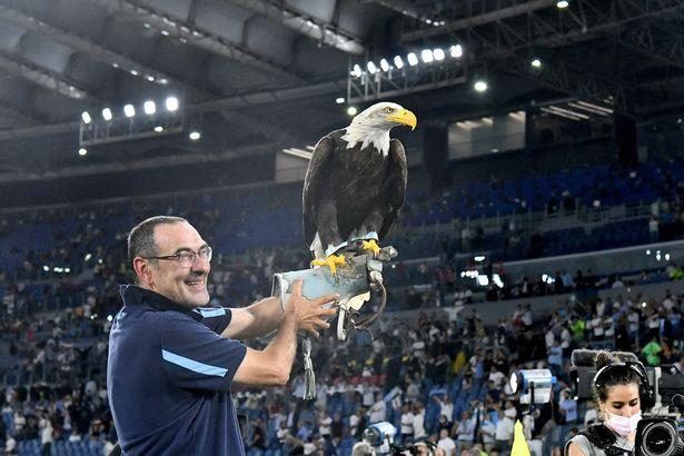 Lazio's Italian coach Maurizio Sarri celebrates with Lazio's eagle mascotte Olimpia at the end the Italian Serie A football match Lazio vs AS Roma at the Olympic stadium in Rome on September 26, 2021.
