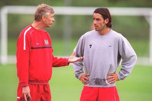 Arsene Wenger the Arsenal Manager chats to Robert Pires of Arsenal during the Arsenal 1st team training session on September 16, 2002 in St. Albans, England.
