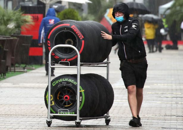 A member of the Scuderia Ferrari team moves tires in a paddock area at the Sochi Autodrom racing circuit hosting the 2021 Formula One Russian Grand Prix. The third practice session of the 2021 F1 Russian Grand Prix has been canceled amid heavy rains in Sochi.