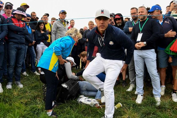 US golfer Brooks Koepka (R) reacts next to injured spectator Corine Remande who was struck by his tee shot during his fourball match on the first day of the 42nd Ryder Cup at Le Golf National Course at Saint-Quentin-en-Yvelines, south-west of Paris on September 28, 2018.
