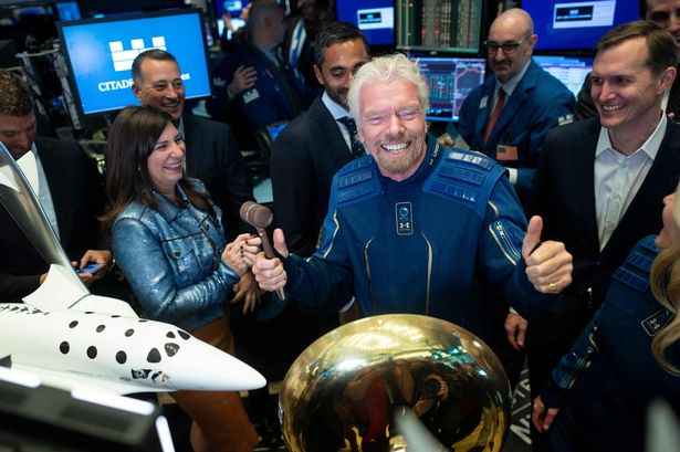(FILES) In this file photo taken on October 28, 2019 Richard Branson, Founder of Virgin Galactic (C) poses next to George T. Whitesides (R), CEO of Virgin Galactic Holdings after ringing the First Trade Bell to commemorate the company's first day of trading on the New York Stock Exchange (NYSE) in New York City. - British billionaire Richard Branson plans to travel to space as early as July 11 aboard a Virgin Galactic spacecraft, his company said in a statement on July 1, 2021. If the schedule holds, Branson would make it to the cosmos before rival billionaire Jeff Bezos, the Amazon founder who said he would travel to space aboard a spacecraft belonging to his company Blue Origin on July 20. (Photo by Johannes EISELE / AFP) (Photo by JOHANNES EISELE/AFP via Getty Images)