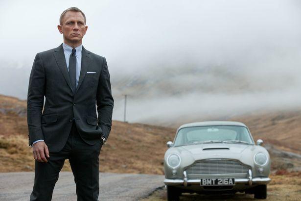 Daniel Craig as James Bond, seen here as 007 in the 2012 film Skyfall, next to his Aston Martin DB5